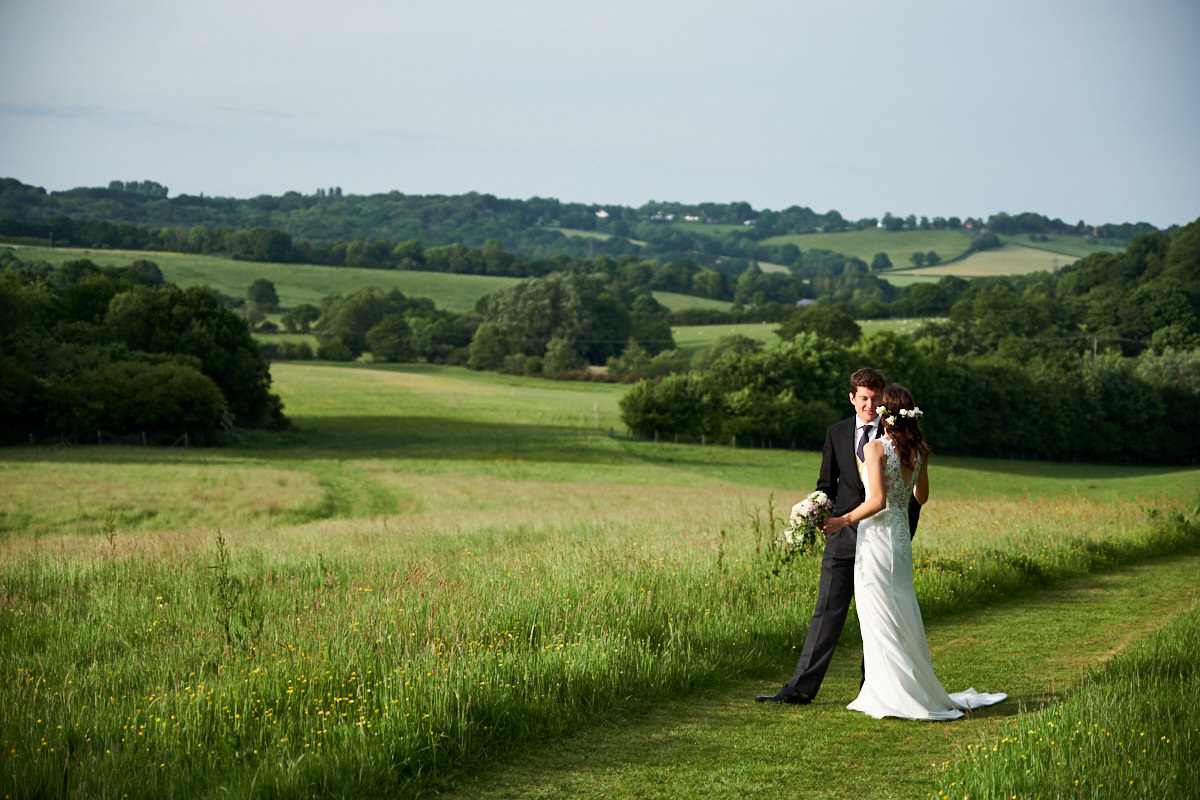 a bride and groom with Sussex countryside behind them