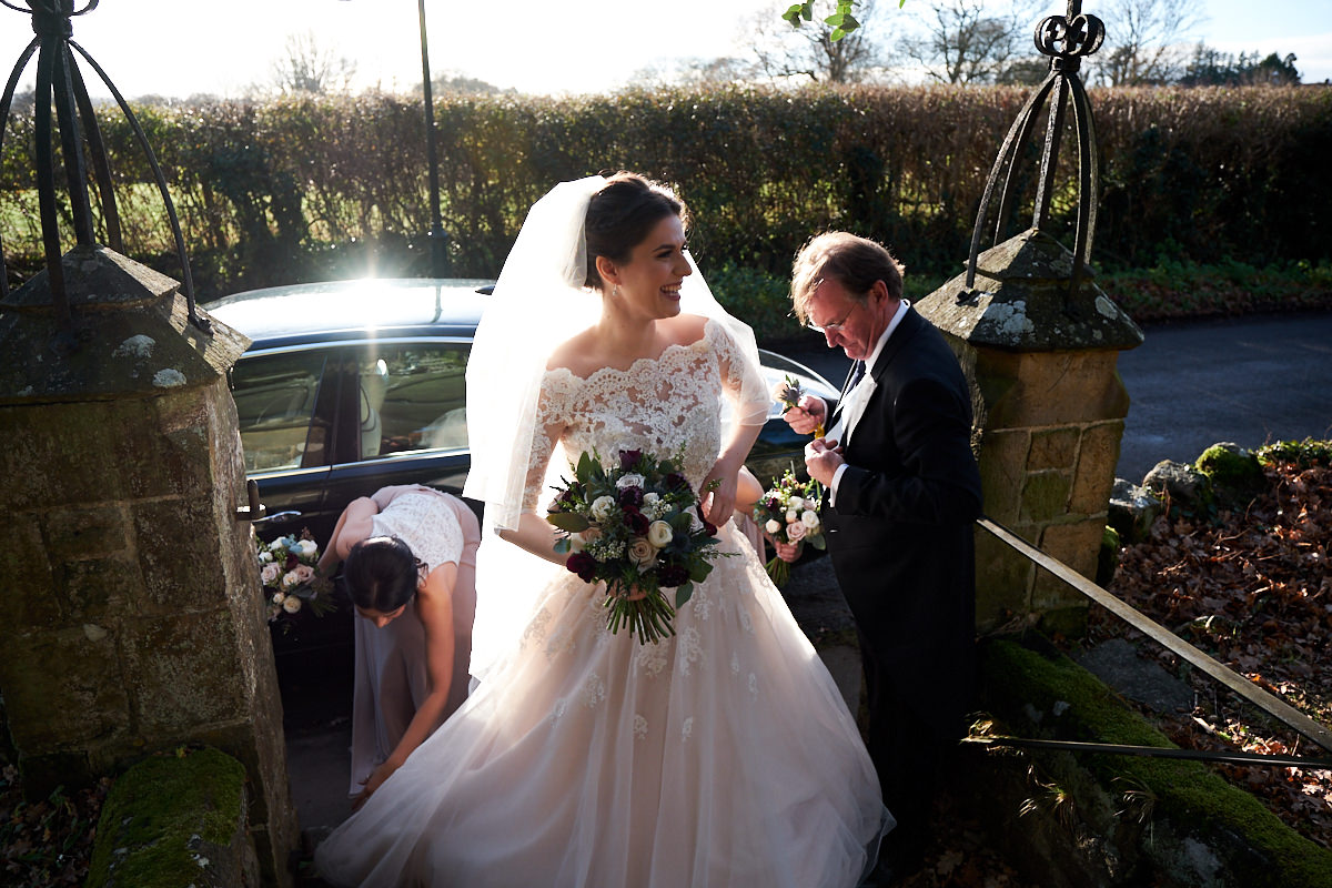 a bride arriving at church with the sun behind her