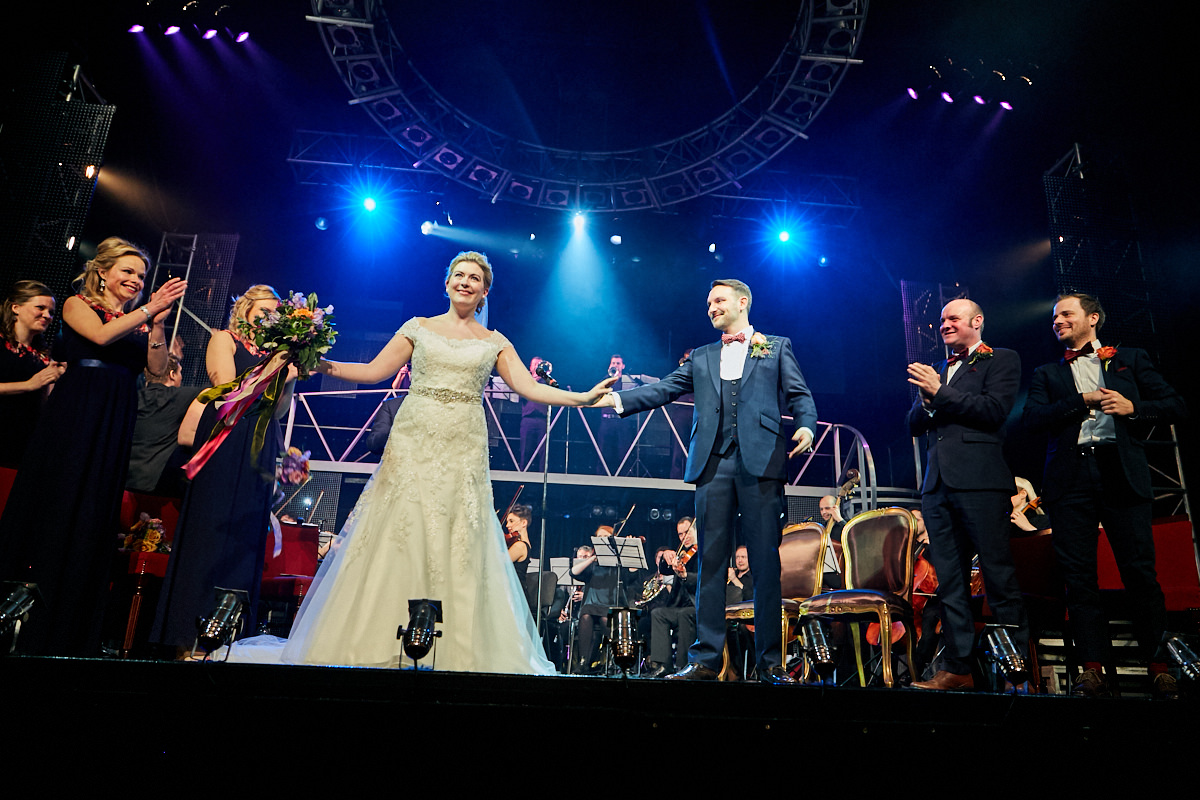 a bride and groom take a bow at the end of their wedding ceremony in a theatre