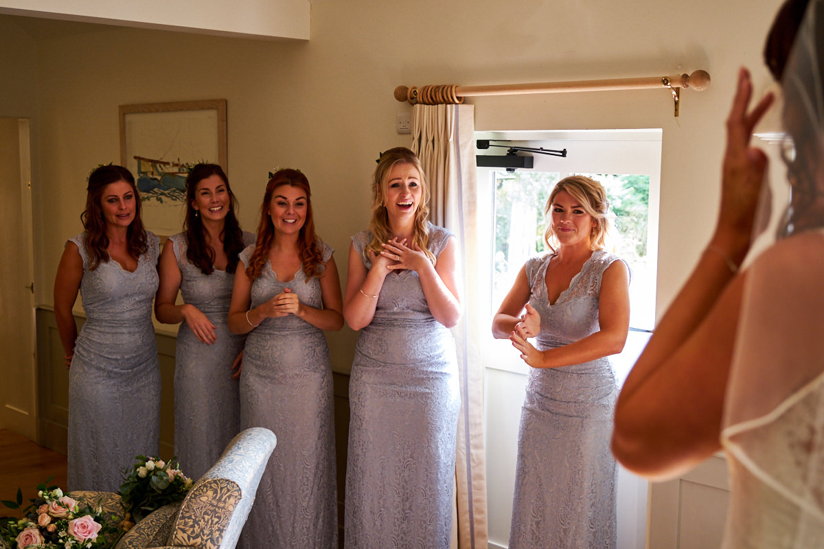 the bridesmaids seeing the bride in her wedding dress for the first time
