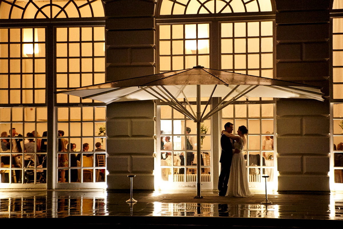 a bride and groom outside The Orangery at Kew Gardens