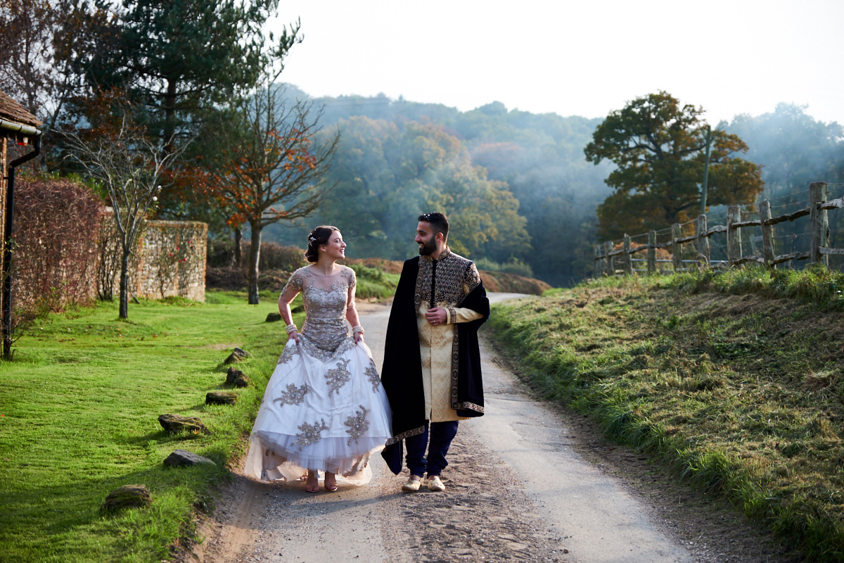a bride and groom walking along a country lane at Selden Barn in West Sussex