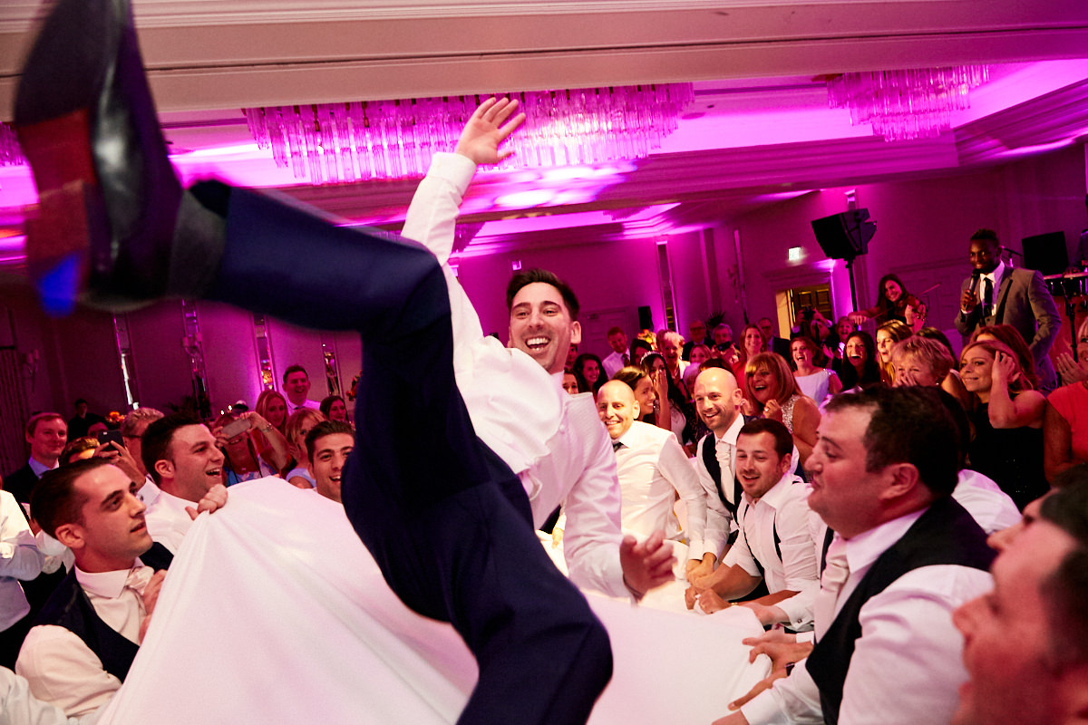 a groom being thrown up in the air in a sheet at a Jewish wedding