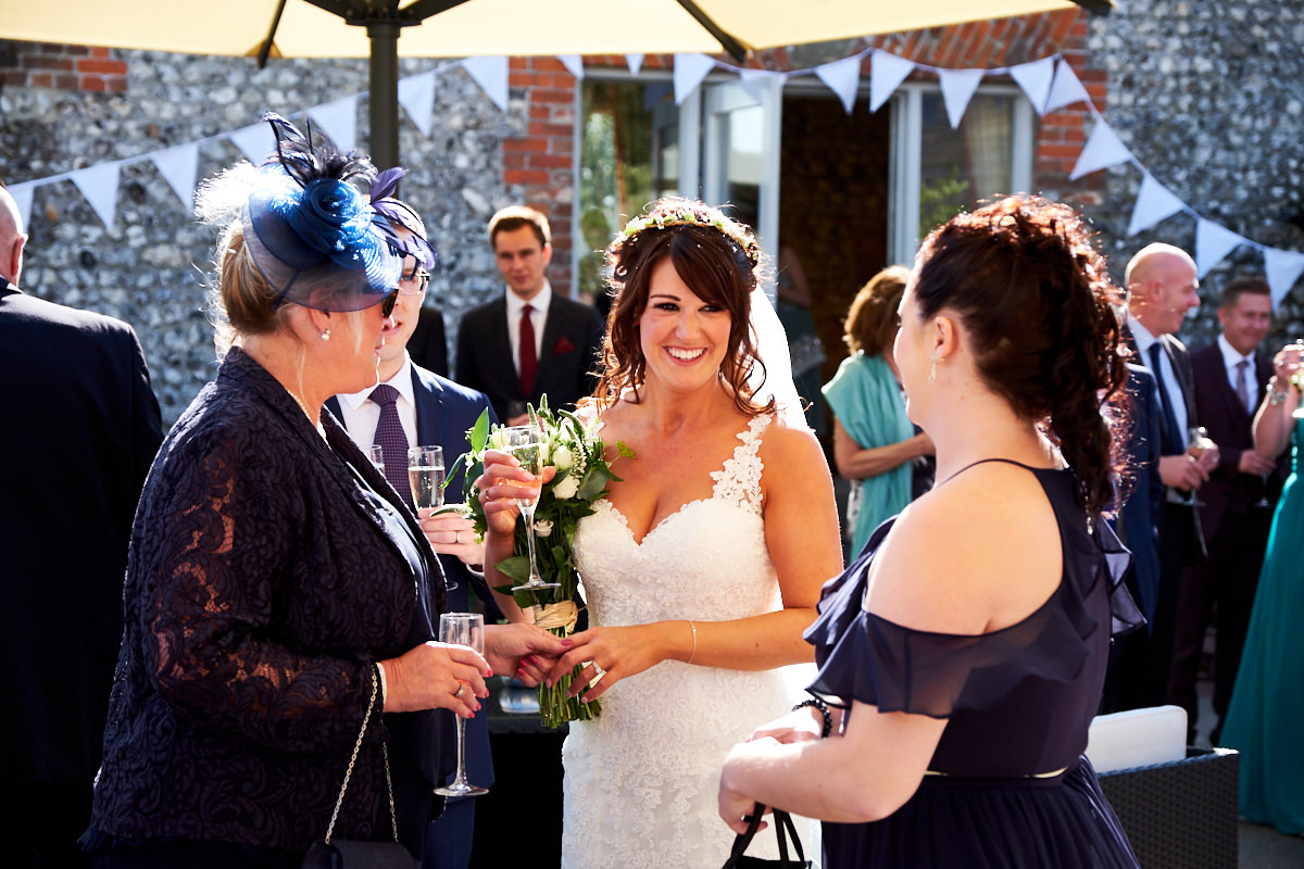 a bride talking to guests at her wedding at Farbridge in West Sussex