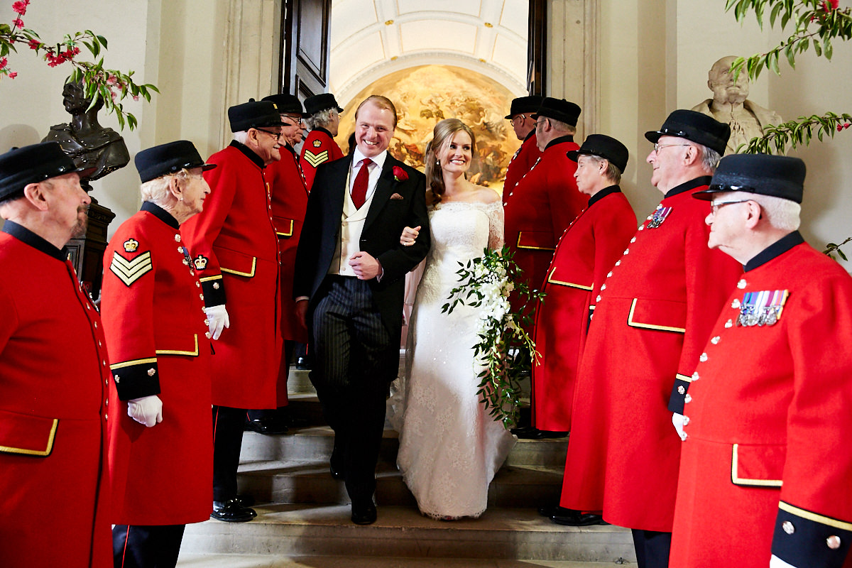 a bride and groom leaving the Wren Chapel at the Royal Hospital Chelsea with Chelsea Pensioners lining the route
