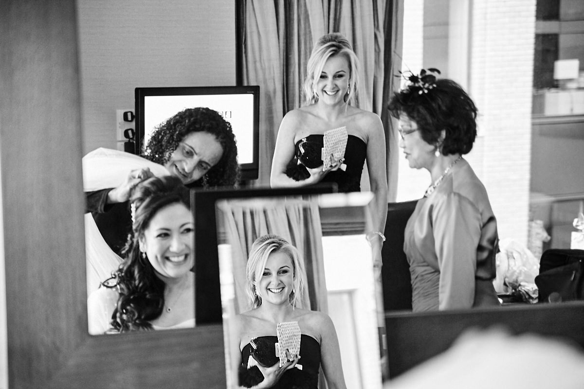 the bride and her bridesmaids reflected in the mirror