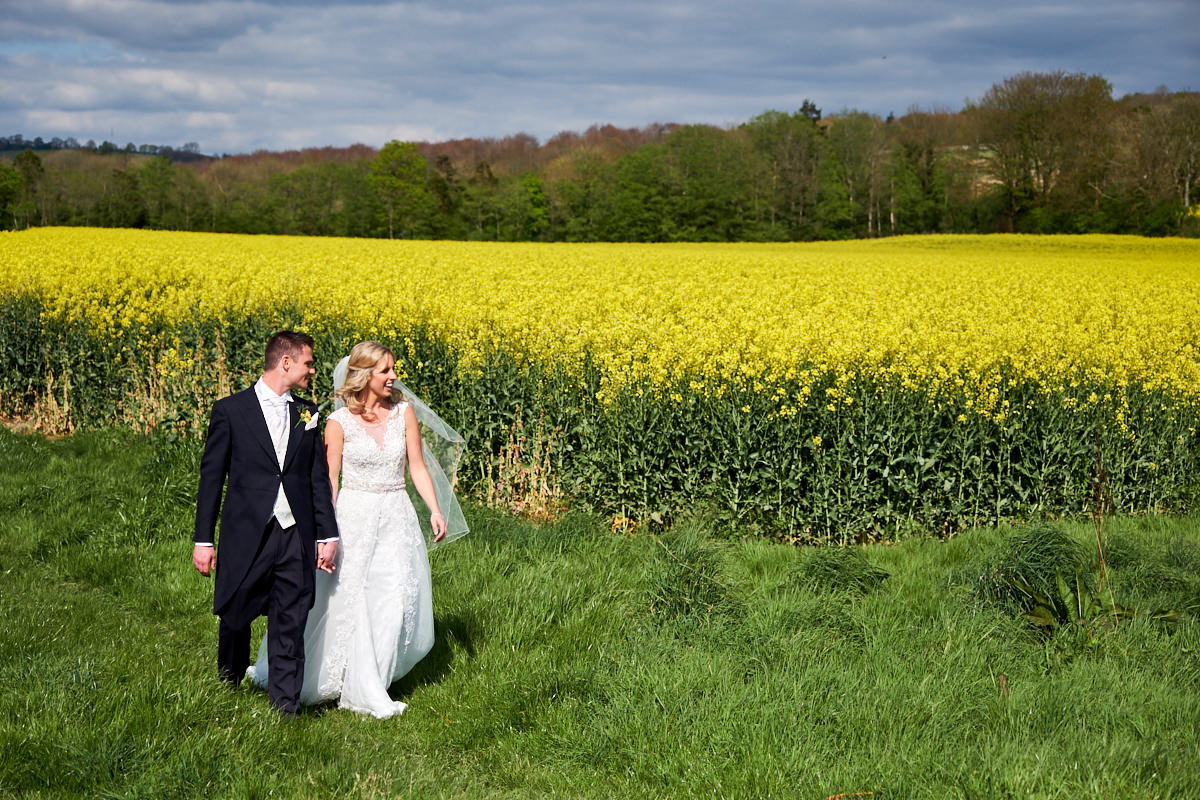 a bride and groom in a field in West Sussex
