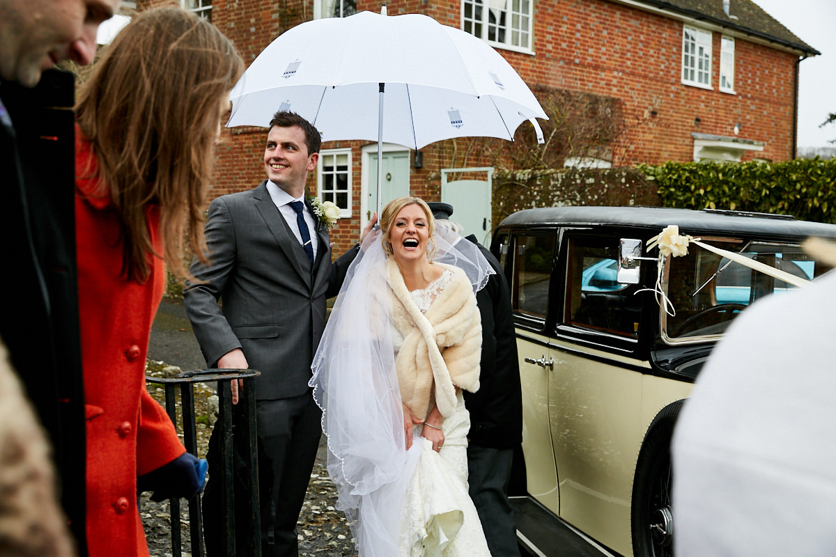 a bride laughing in the rain as her new husband holds the umbrella