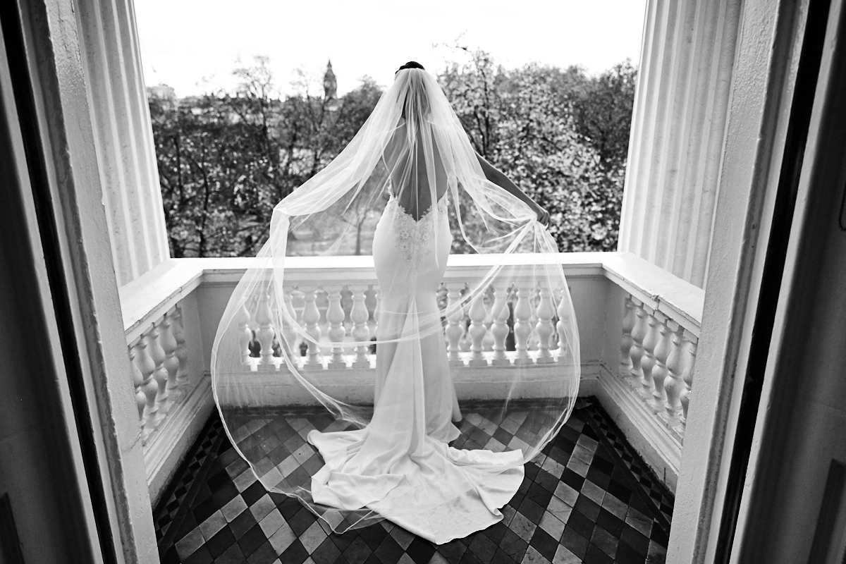 a bride on a balcony with her veil blowing behind her