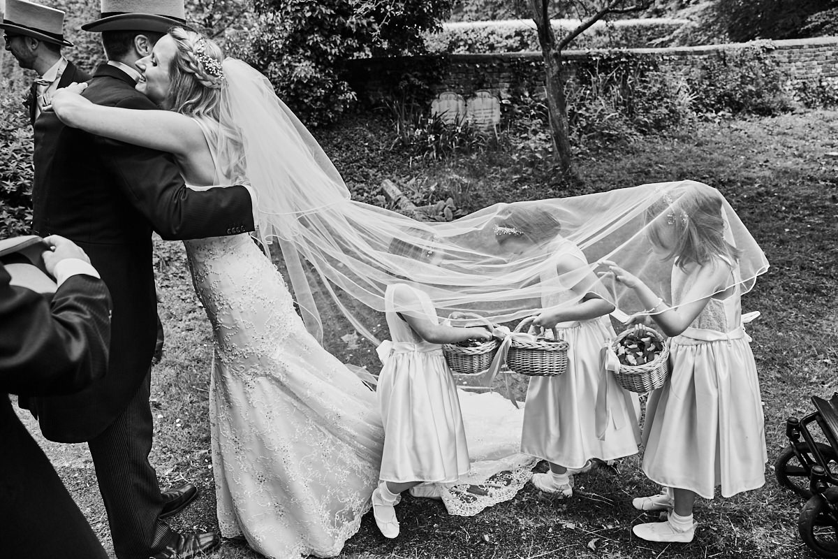 a bride hugs a guest while the flower girls hide under her veil