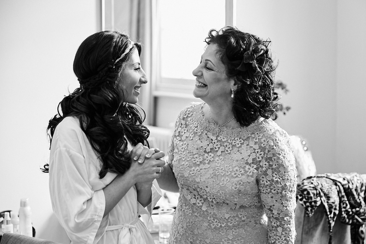 the bride and her mother smiling at each other