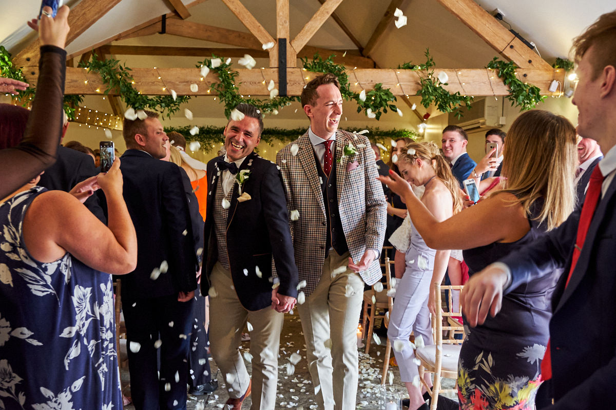 the grooms walking out of the ceremony with lots of confetti being thrown at them