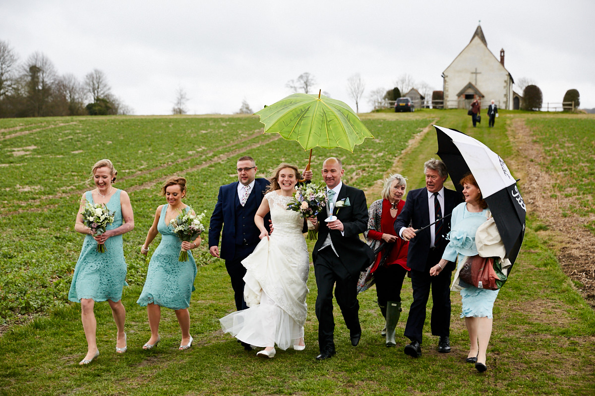 The bride and groom and guests walking down the hill outside a remote church after their wedding ceremony