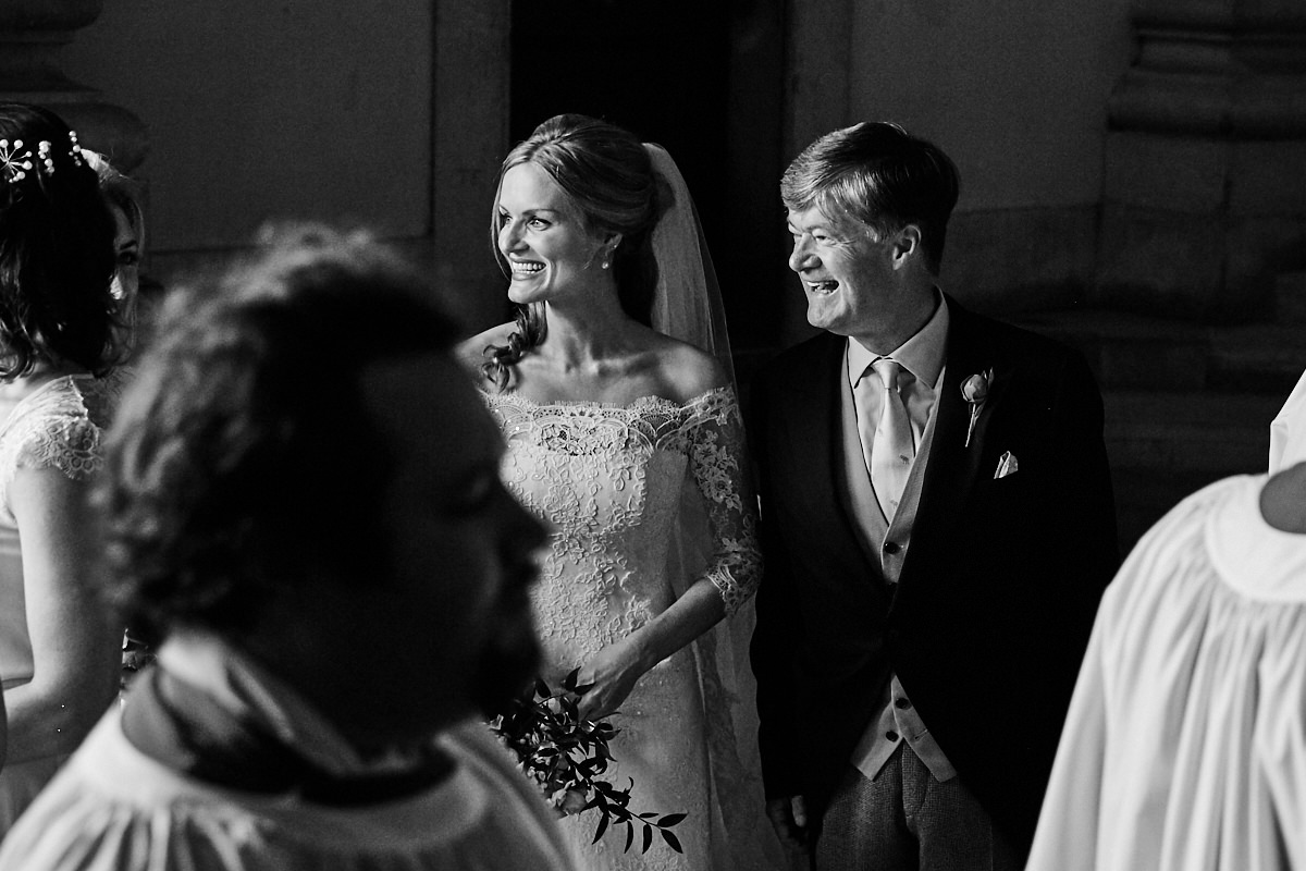 the bride and her father watching the choir enter the chapel before her wedding ceremony