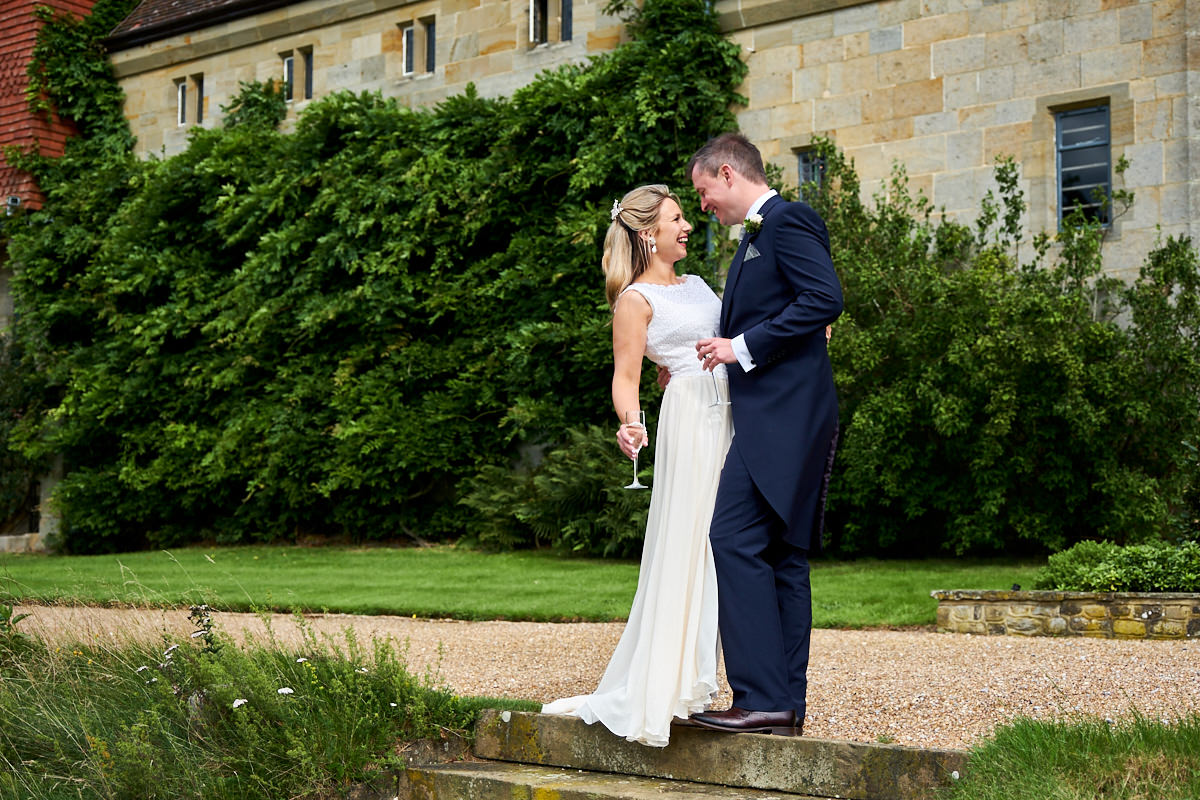 a bride and groom laughing together at their wedding at Cowdray House in Sussex