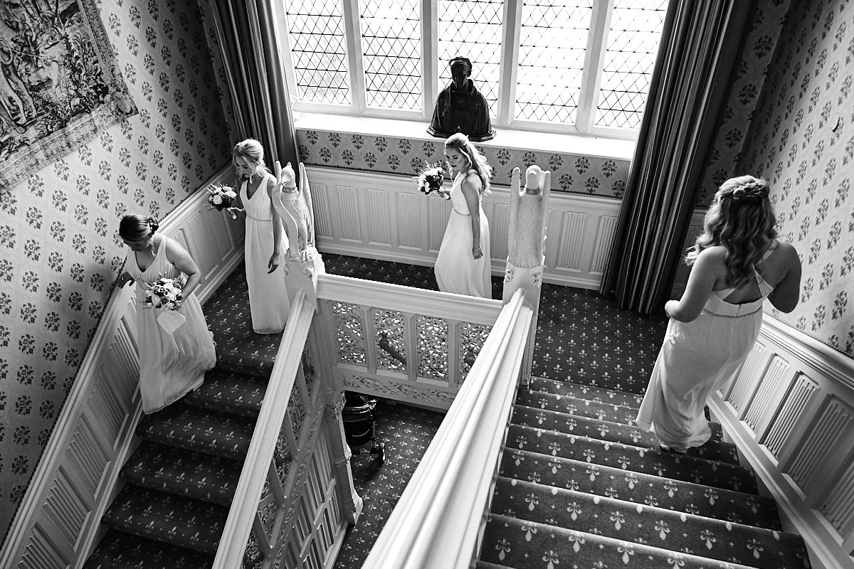 bridesmaids walking down the stairs at Horsted Place in Sussex
