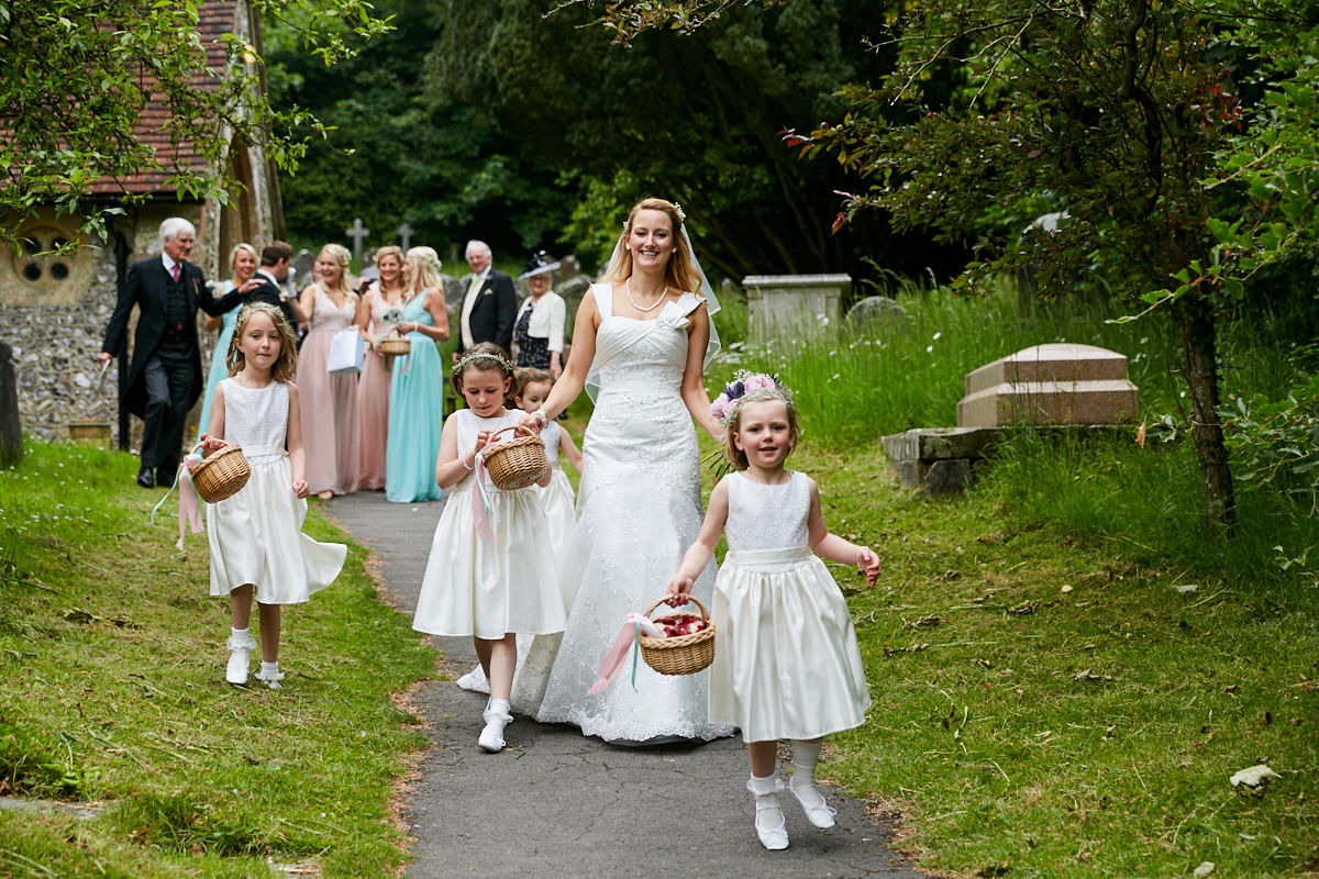 a bride and her flower girls leaving the church after her wedding ceremony