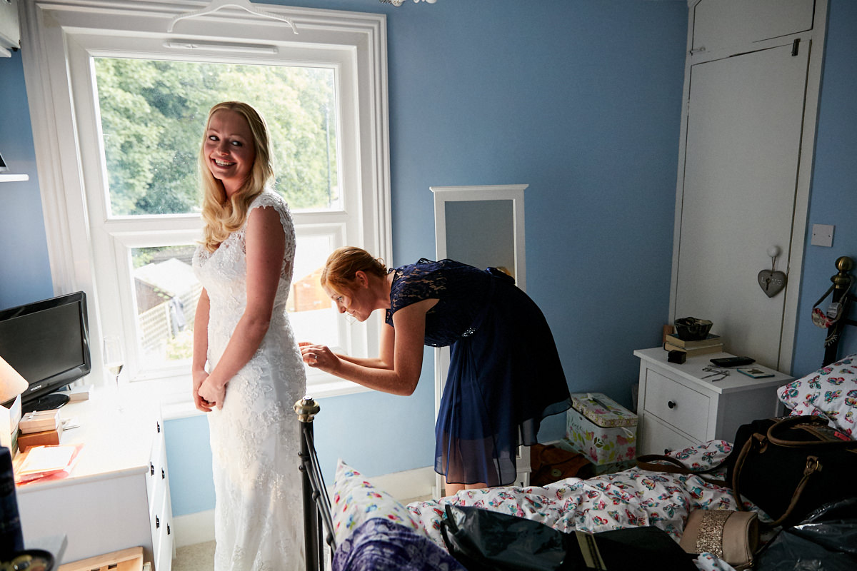 a bride having her dress done up by one of her bridesmaids