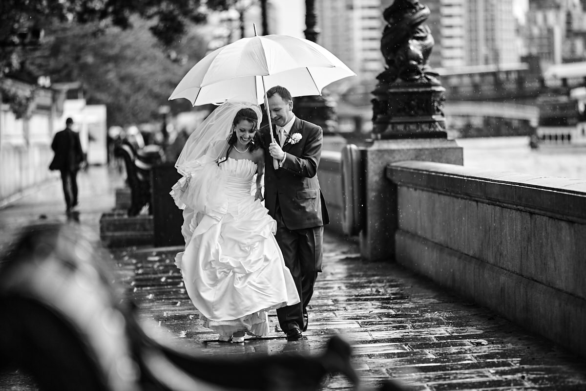 a bride and groom shelter under an umbrella on their wedding day
