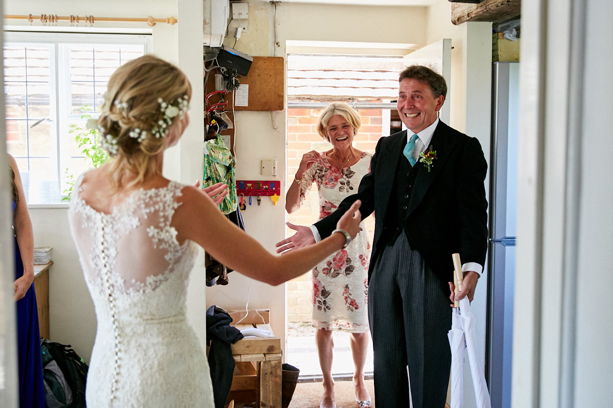 the father of the bride sees her in her wedding dress for the first time
