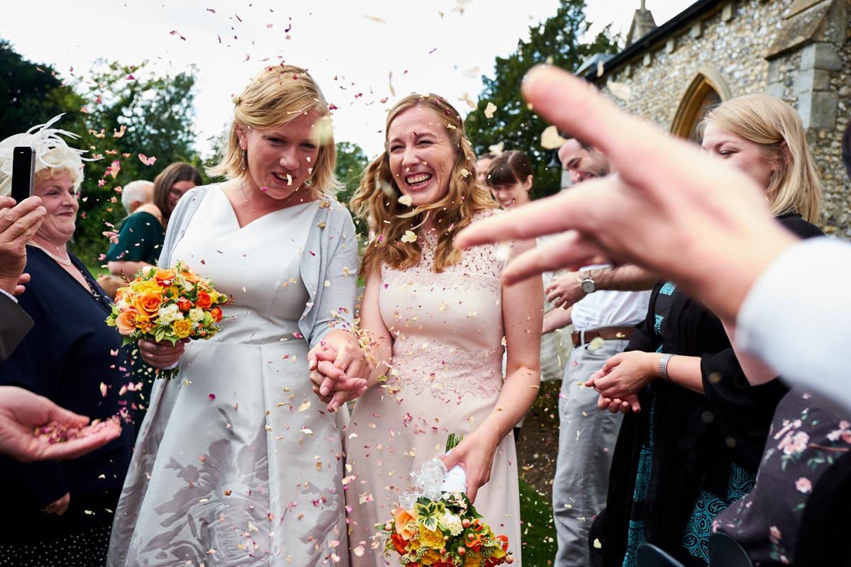 a wedding couple having confetti thrown at them