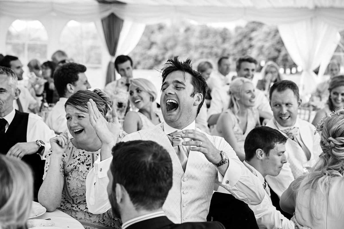 a guest laughing at the best man's speech