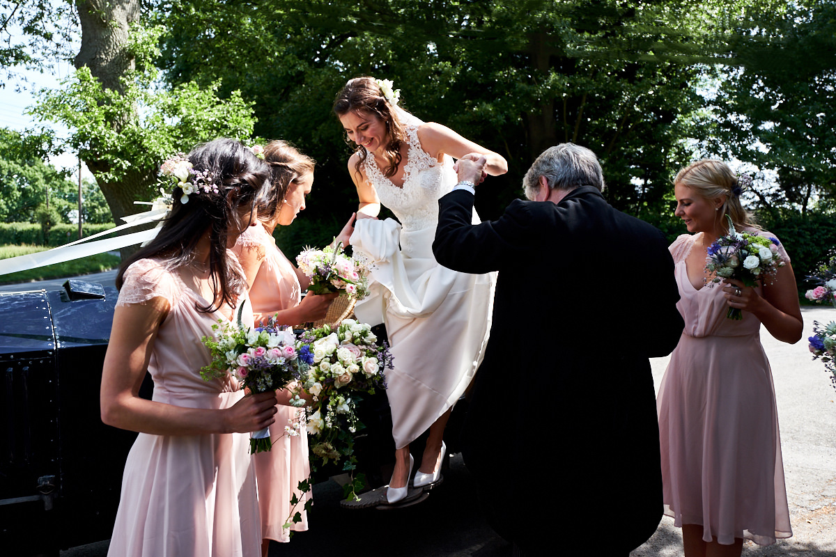a bride getting out of the car at her Sussex wedding