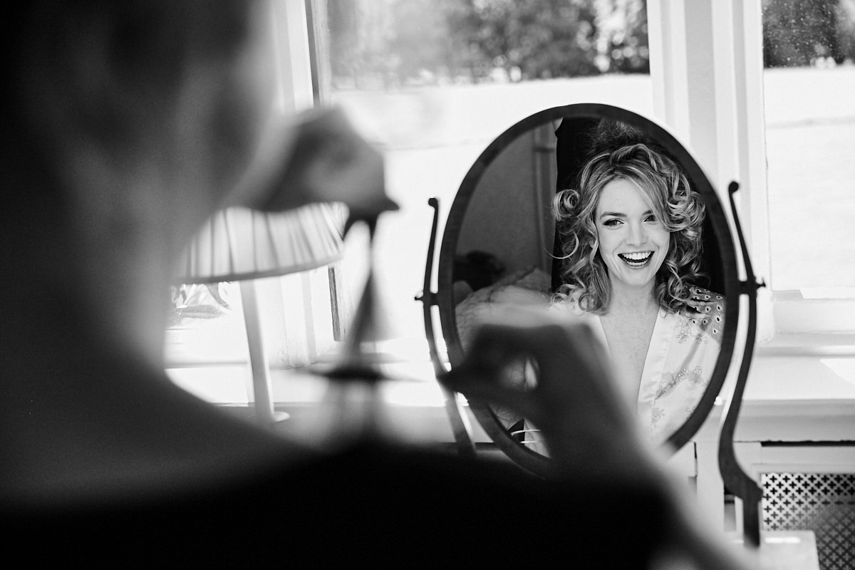 a bride looking in the mirror while she has her makeup done before her wedding ceremony at Horsted Place