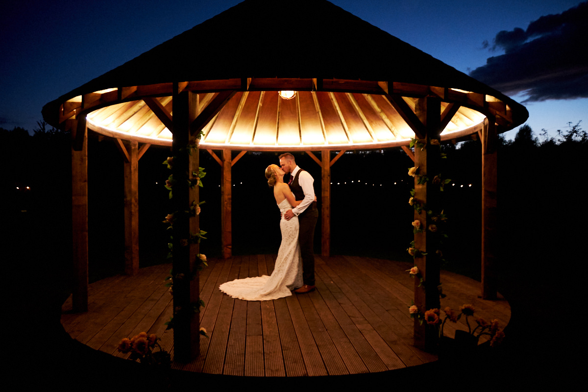 a bride and groom kiss as the sun goes down