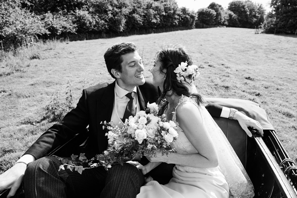 a bride and groom go to kiss each other in the back of an open top car as they drive over fields in Sussex