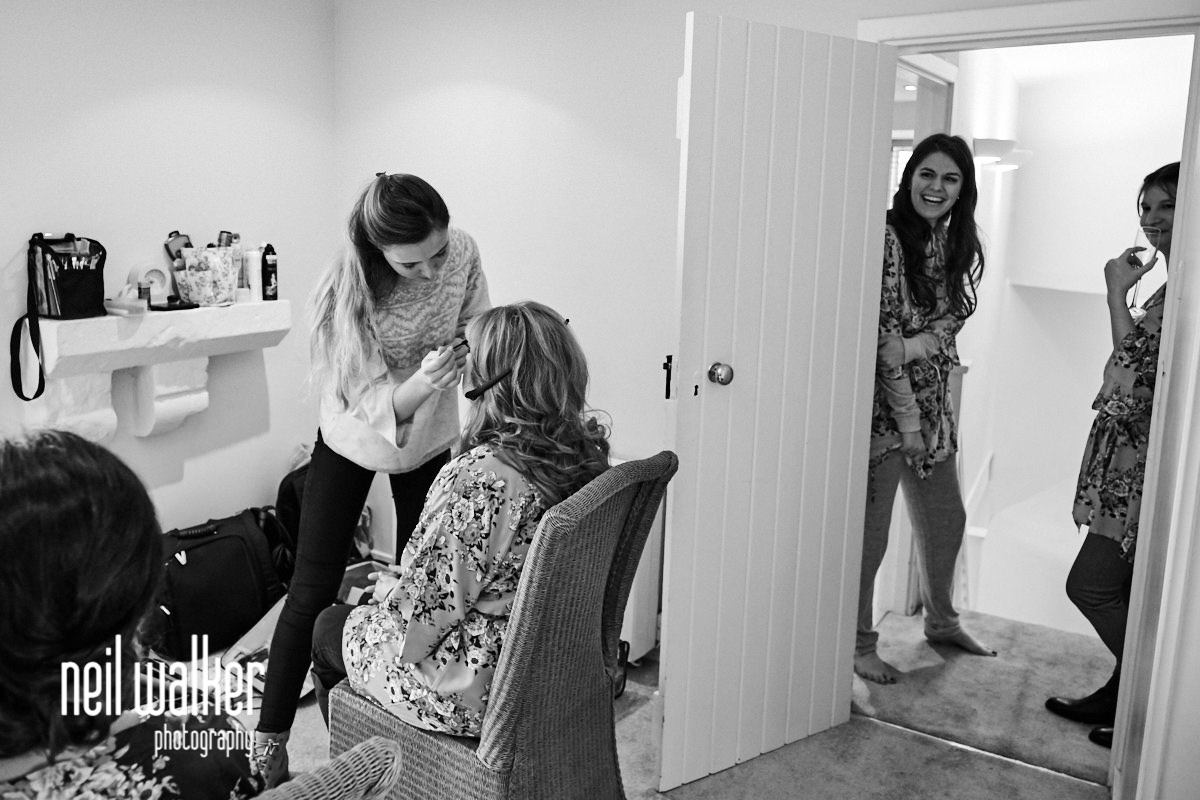 the bride watching her bridesmaids having their makeup done
