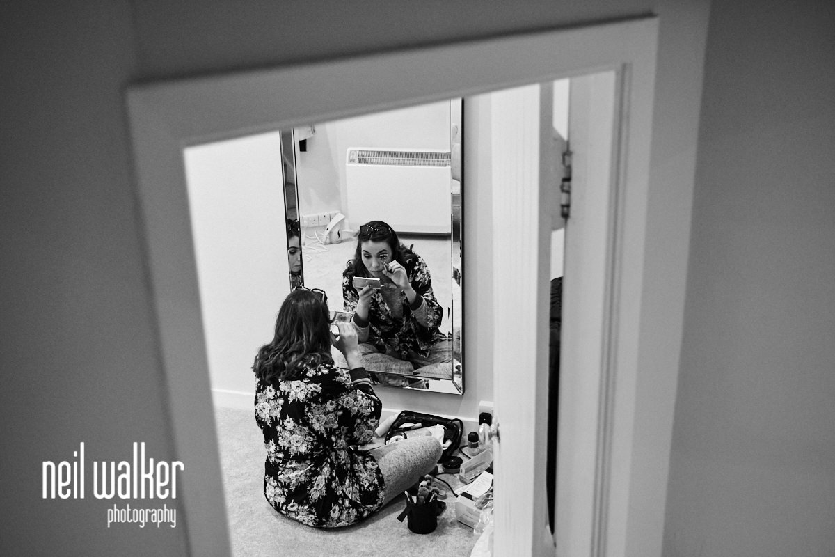 a bridesmaid doing her makeup in the mirror
