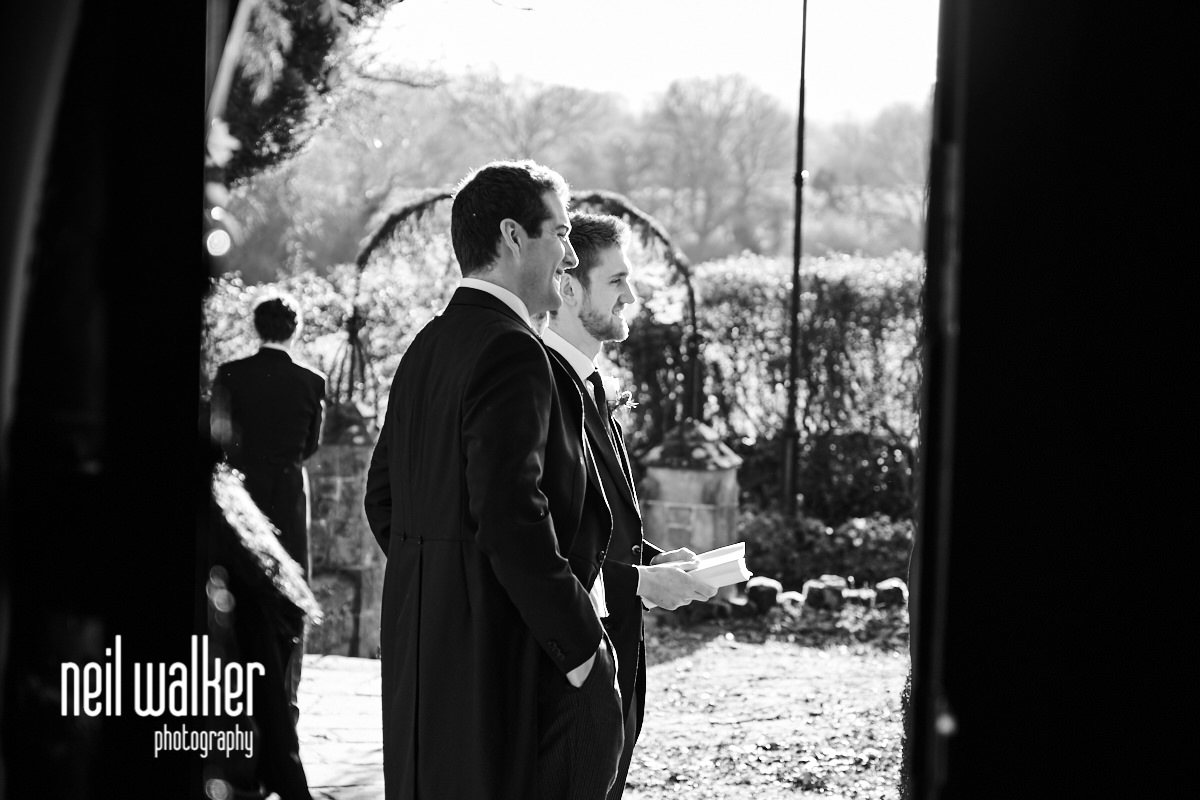 the groom waiting for his guests outside the church