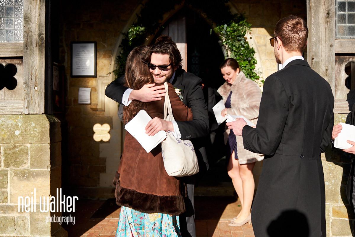 a groomsman hugging a guest