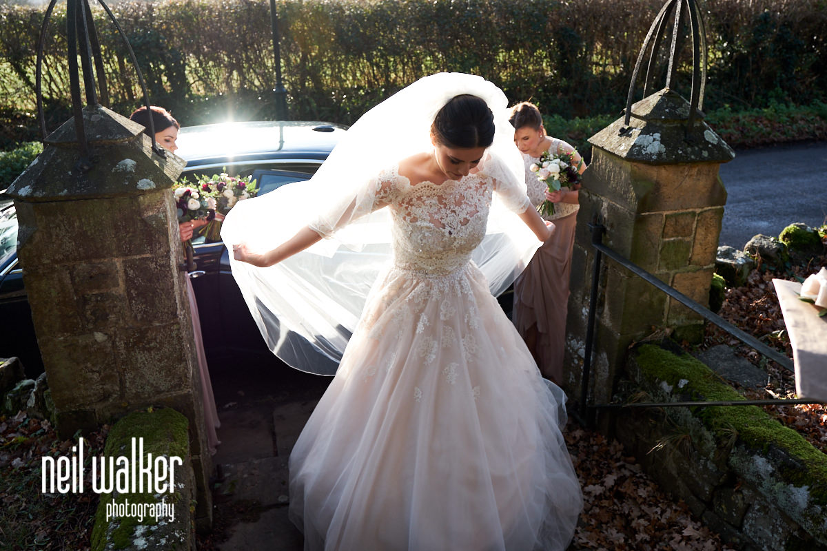 the bride arranging her dress after getting out of her wedding car