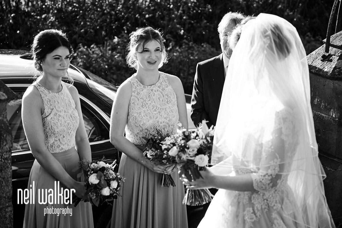 a bridesmaid smiling at the bride