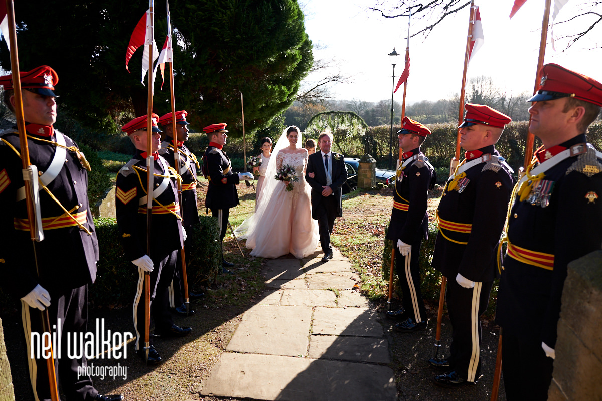 the bride walking towards the church with her father