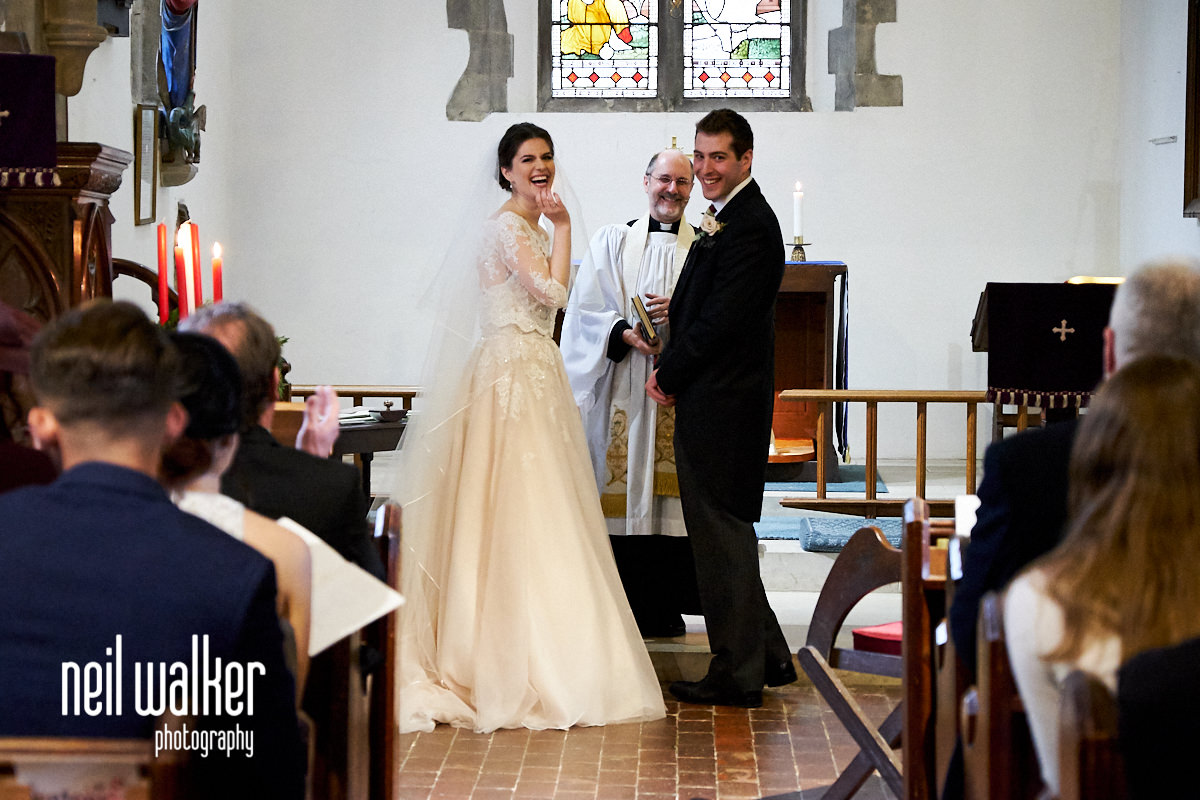 the bride and groom looking at the congregation and laughing