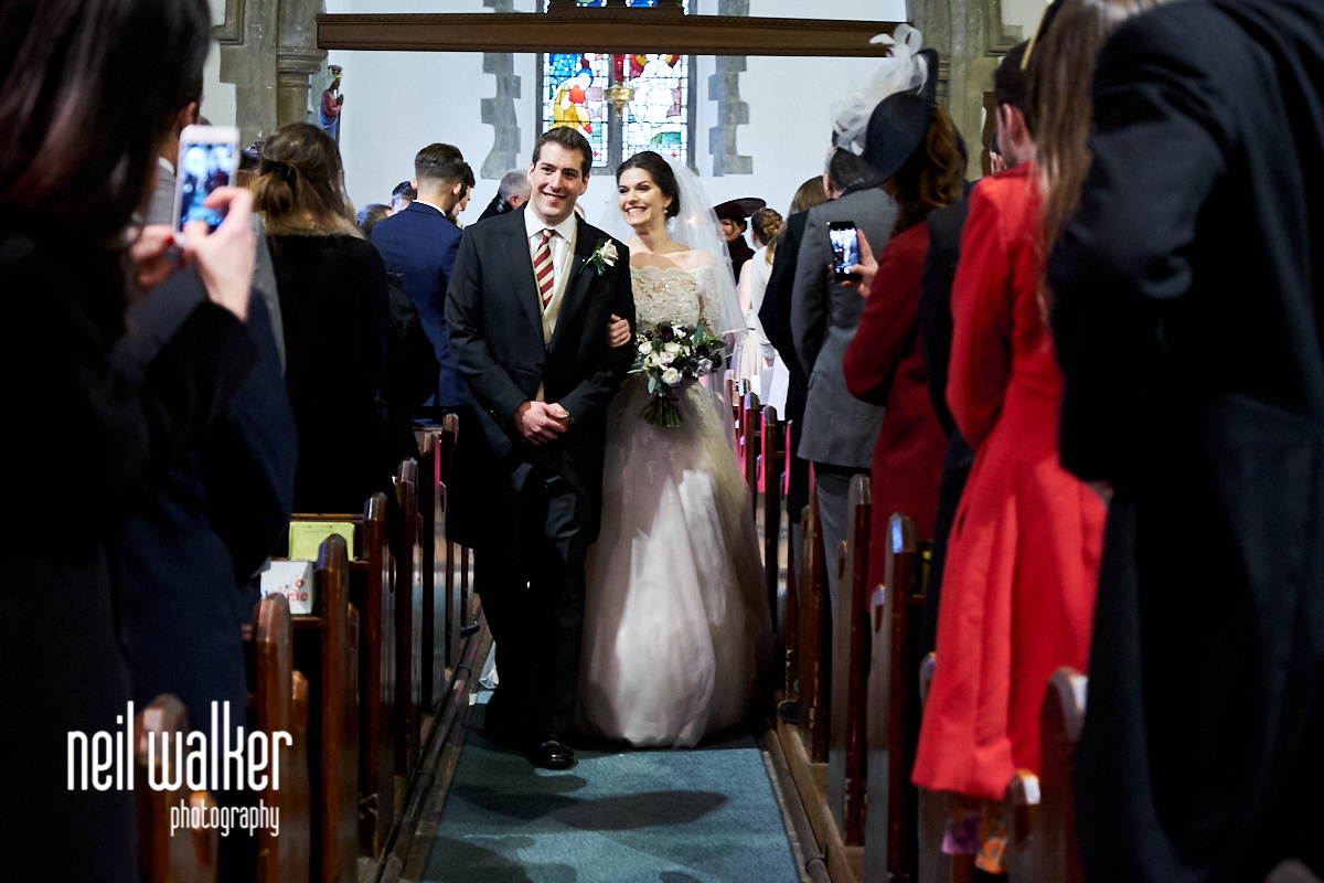 the bride and groom walk down the aisle together