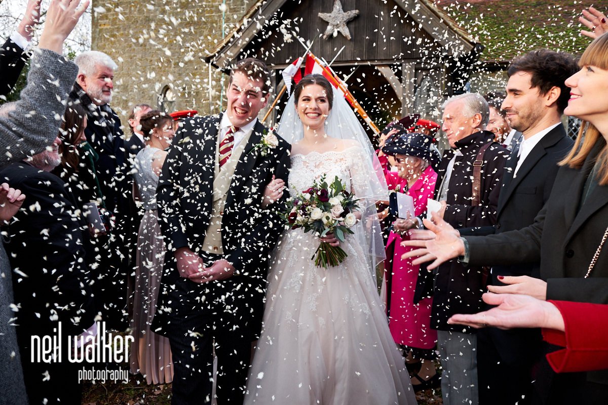 the bride and groom walking through confetti