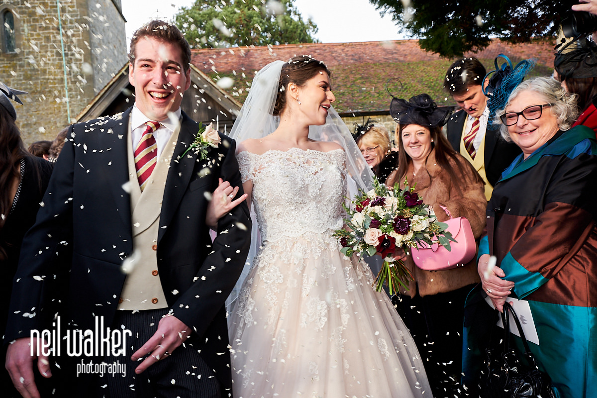 the bride and groom having confetti thrown at them by guests