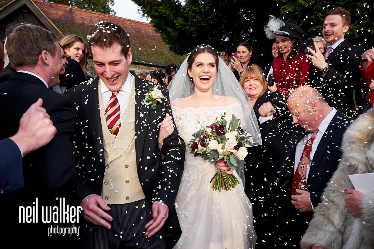 the bride laughing as she walks through confetti