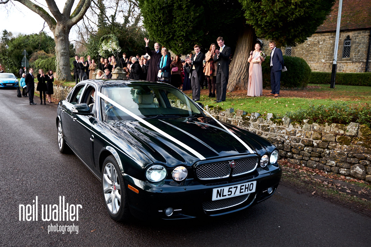 the wedding car pulling away from the church
