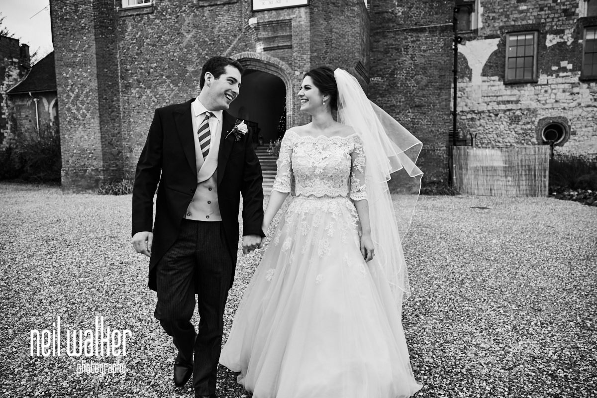 the bride and groom at Farnham Castle walking together