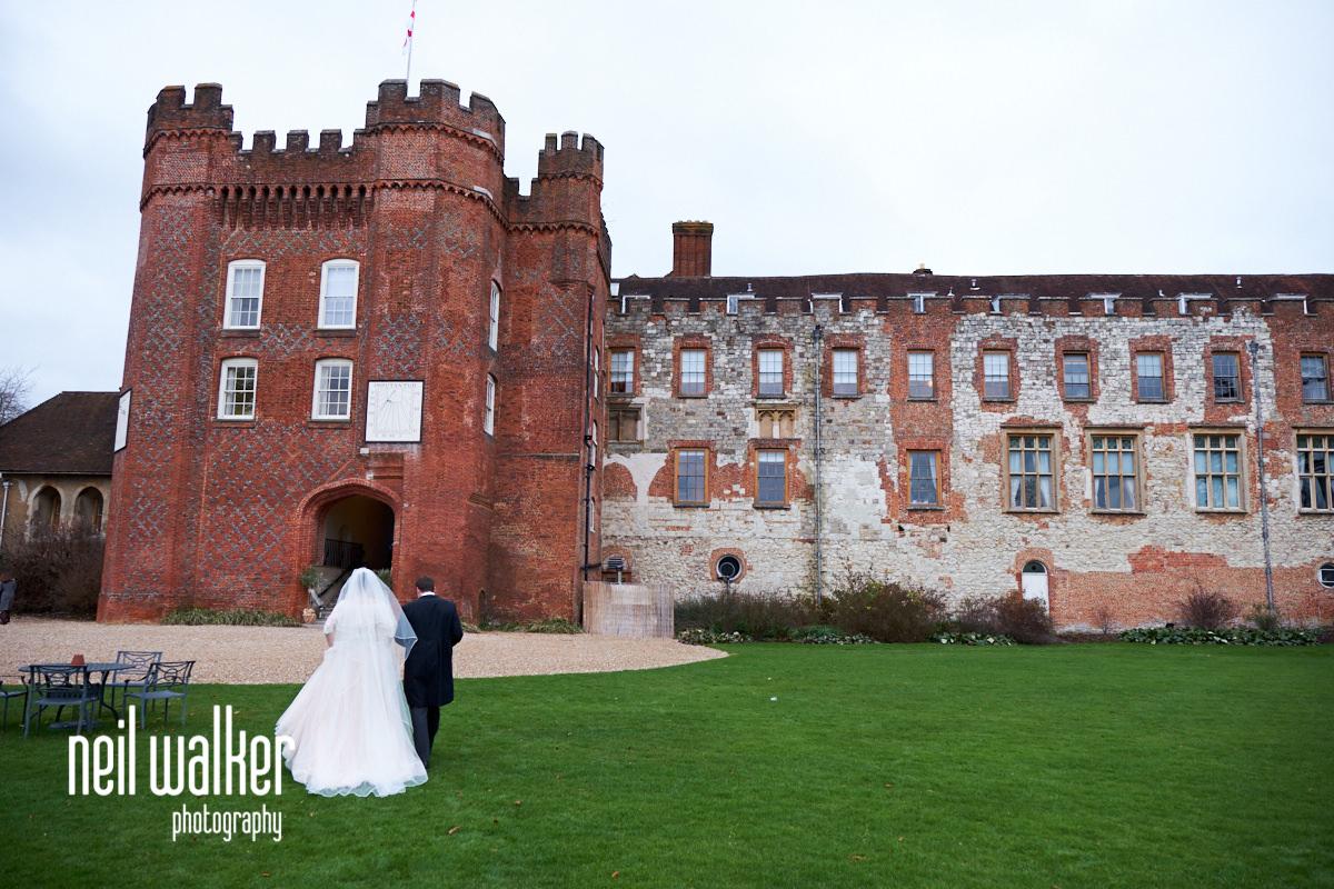the bride and groom walking towards Farnham Castle