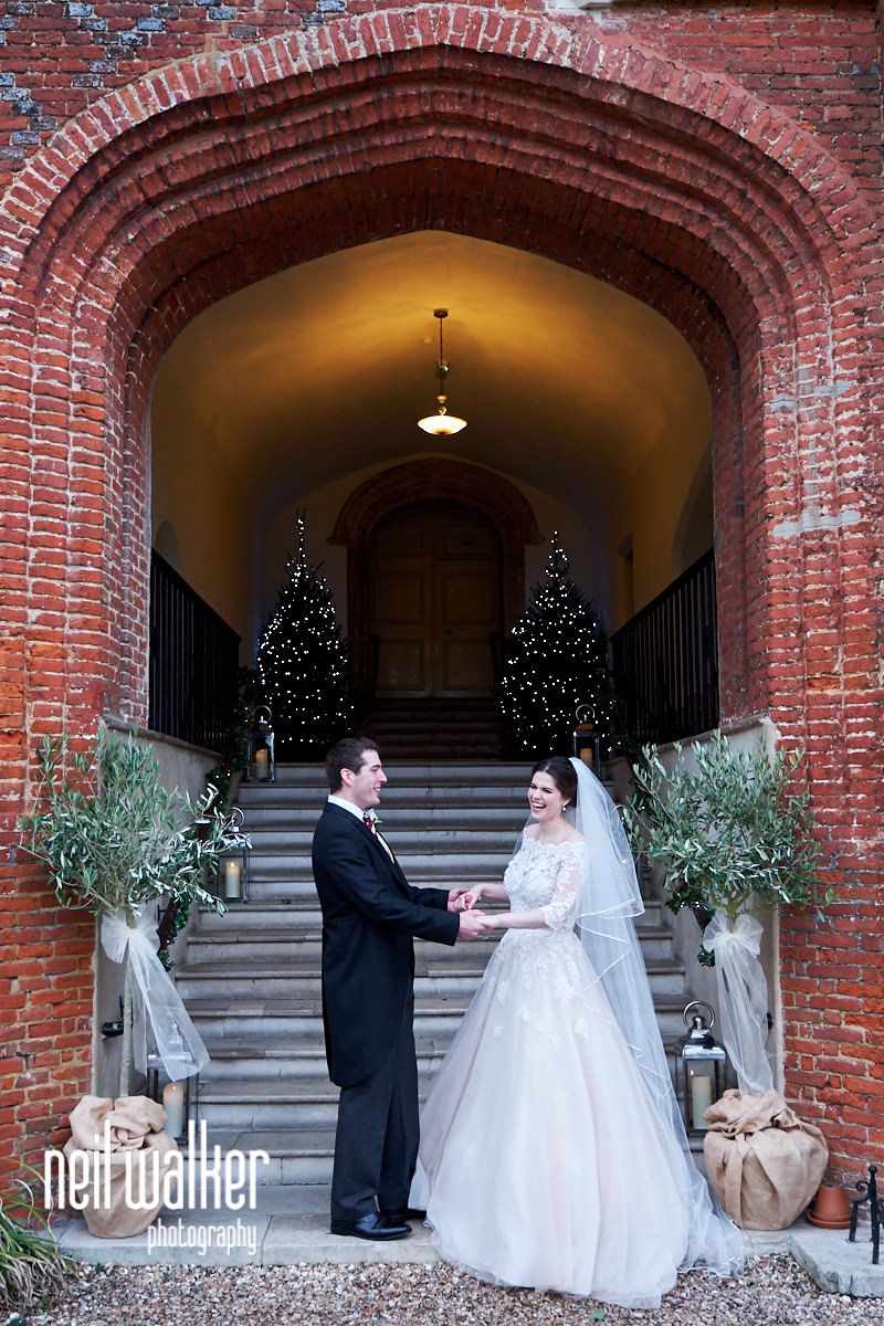 the bride and groom framed by the entrance to Farnham Castle