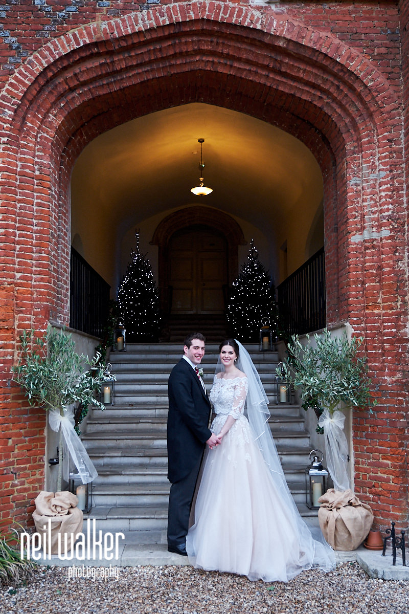 the bride and groom standing by the entrance to Farnham Castle