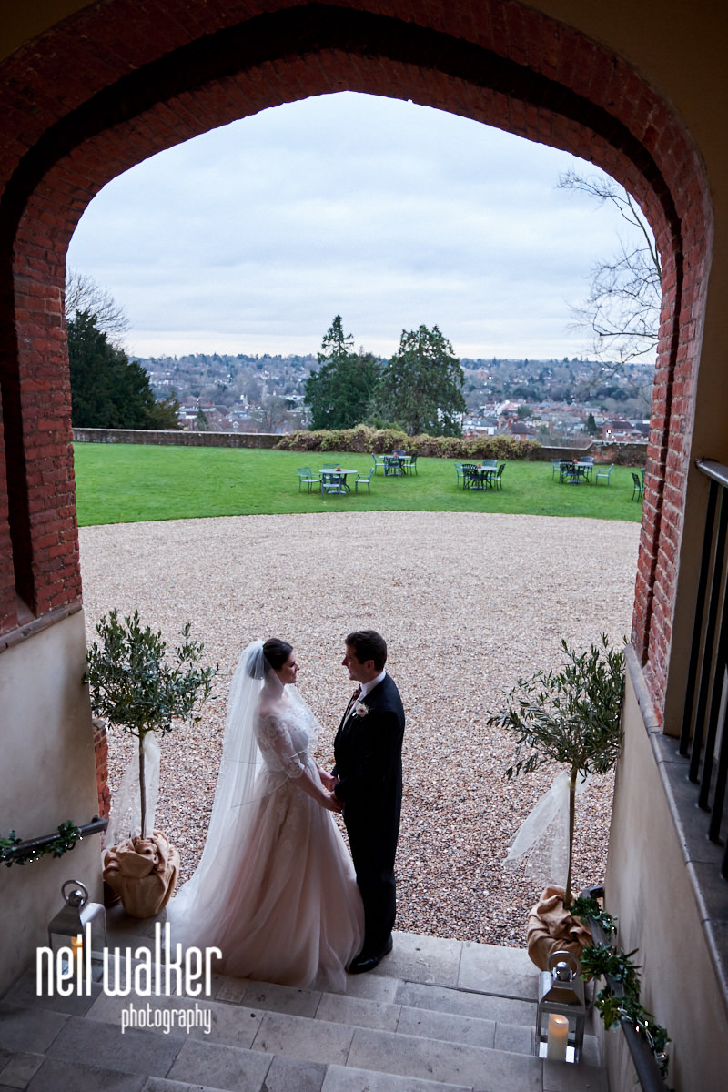 the bride and groom standing with the view from Farnham Castle behind them