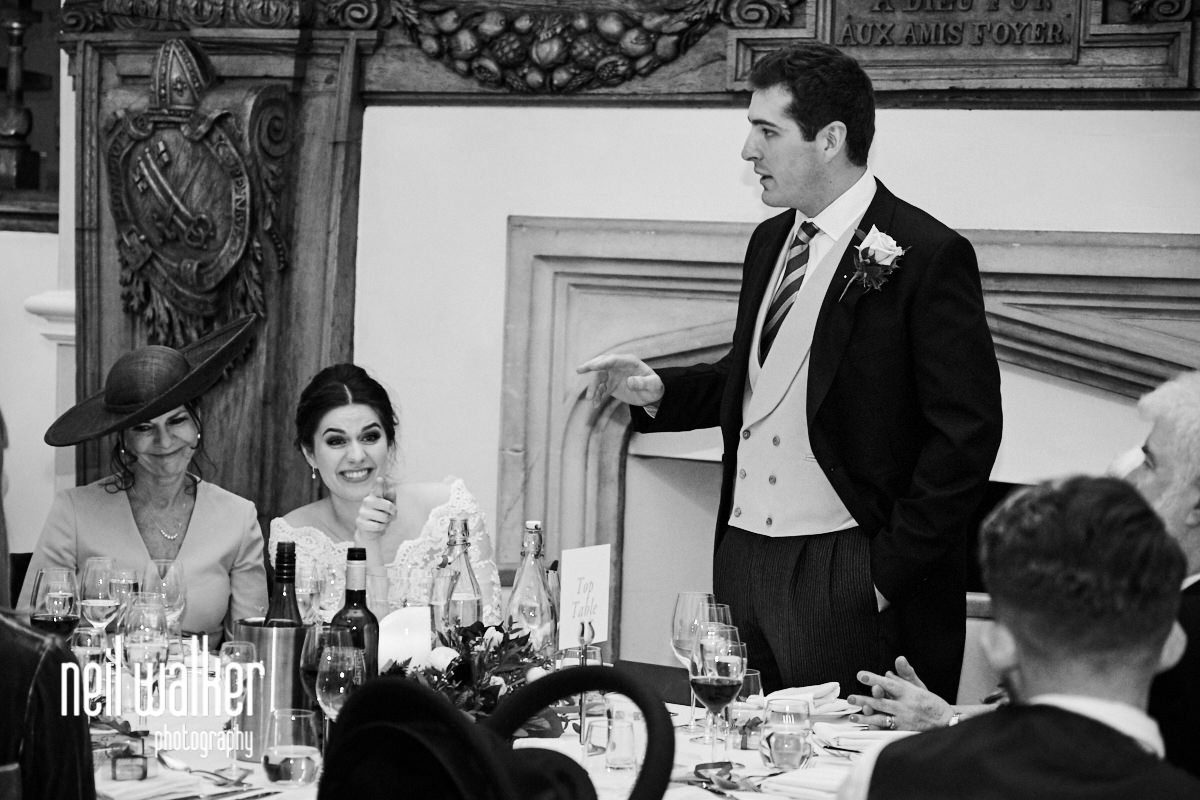the bride laughing as the groom makes a speech