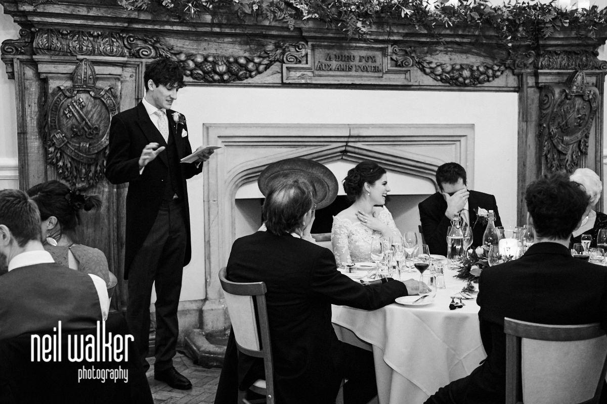 the groom grimacing during the best man's speech